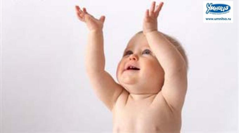 Ребенок 7 месяцев рассматривает свои руки
